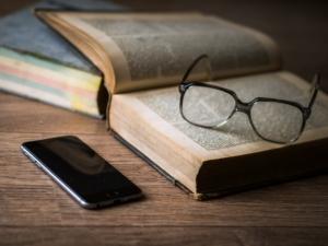 Medien mit Brille, Buch und Handy